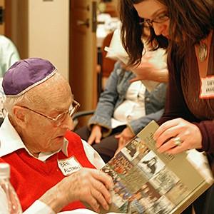 volunteer and survivor looking at a book